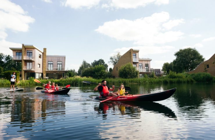 Family with kayaks and paddle board crossing the lake at Lower Mill Estate Cotswolds