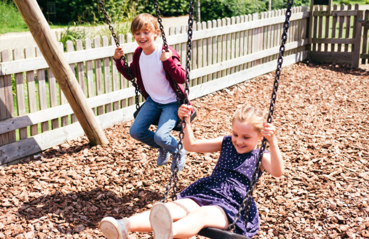 Children on the swings at Lower Mill Estate in the Cotswolds